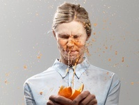 Woman splashed with juice from orange, studio shot 20056004474| 写真素材・ストックフォト・画像・イラスト素材|アマナイメージズ