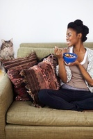 Young woman having breakfast, looking at cat
