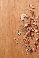 Sharpener and pencil shavings on wooden background