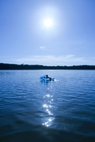 Boy swimming in lake with an inflatable dolphin, Brandenburg
