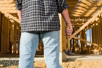 Man with hammer in front of frame of new house