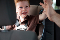 Boy in car reaching out to adult hand
