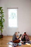Couple sitting on rug with magazines