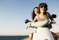 Smiling women riding scooter on beach