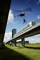 Man jumping from helicopter to train