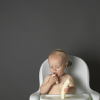 Baby in high chair eating a banana