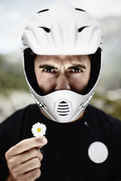 Man in motorcycle helmet holding daisy