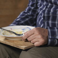 Older man eating on tray