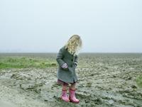 Girl wearing rainboots on beach