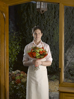 Man in apron holding bouquet in doorway