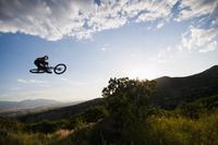 Mountain biker jumping on hillside
