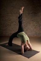 Woman practicing yoga on mat 20056007152| 写真素材・ストックフォト・画像・イラスト素材|アマナイメージズ