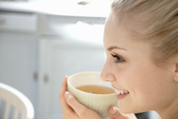 Smiling woman having cup of tea