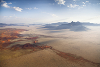 Aerial view from hot air balloon over magnificent desert landscape of sand dunes, mountains and Fairy Circles, Namib Rand game r