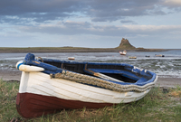 Fishing boat pulled onto the shore at Holy Island, looking towards the castle, Lindisfarne, Northumberland, England, United King