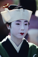 Portrait of a woman with white face make-up and hat of the Festival of Ages in Kyoto, Japan, Asia
