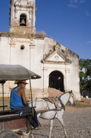 A man with horse and buggy passing an old church in Trinidad, Cuba, West Indies, Central America