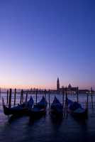 Gondolas at sunrise and San Giorgio Maggiore in silhouette in the background, Venice, UNESCO World Heritage Site, Veneto, Italy,