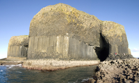 Columnar basalt lava with Fingal's Cave cut into it by sea, Staffa, off west coast of Mull, Inner Hebrides, Scotland, United Kin