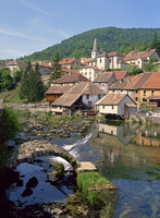 The weir and remains of a medieval bridge on the River Loue, with the houses and church of the village of Lods in Franche-Comte,