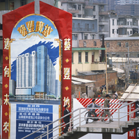Sign showing modern buildings in front of old huts and apartment blocks in the Shenzhen Development Zone, Guangdong, China, Asia