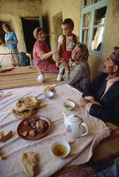 Tajik family at table with typical offering of mutton, tea and bread, near Ayni, Tajikistan, Central Asia, Asia