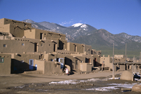 Lady sweeps up after visitors have departed, multistorey adobe buildings in north complex dating from around 1450 AD, Taos Puebl