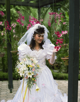 Bride looking at orchids, Asia 20062011327| 写真素材・ストックフォト・画像・イラスト素材|アマナイメージズ