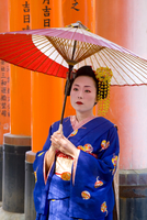 Portrait of a geisha holding an ornate red umbrella in front of a line of red torii gates, Fushimi-Inari Taisha, Kyoto, Kansai R 20062012231| 写真素材・ストックフォト・画像・イラスト素材|アマナイメージズ