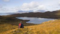 Hiker looking across Loch Dhughaill towards the distant Cuillin Hills, Sleat Peninsula, near Tarskavaig, Isle of Skye, Highland,