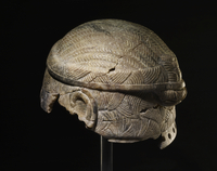 Stone wig or helmet with carved ears; row of bored holes nea