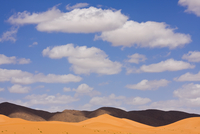 Orange sand dunes, black mountains and blue sky in the Sahar