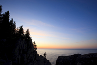 Lone hiker at sunrise on the Bold Coast trail in Cutler, Mai