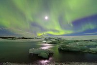 Northern lights (Aurora Borealis) and moon in sky above Joku