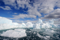 Melting ice under expansive clouds. Floe Edge, Arctic Bay, B