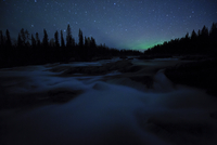 Northern lights far on the horizon in night landscape. Sarek