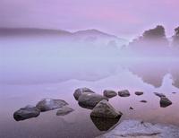 Mist over Coniston Water before dawn. Lake District, Cumbria