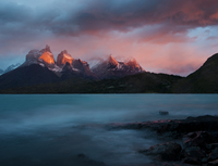 The blue green waters of Lago Pehoe, with the sunset light on Los Cuernos del Paine, in Torres del Paine National Park, Chile