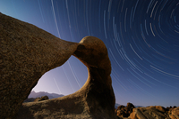 Star trails in sky over Alabama Hills, BLM eroded granite formation know as Mobius Arch. Eastern Sierra, California. May 2012.