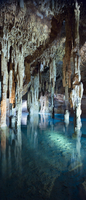 Stalagmites and stalactites in underground cavern with azure waters of Cenote Papakal (sink hole), near Merida, Yucatan, Mexico