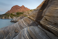 Coastal rock formations with the top of Tomskjevelen in the background, Tomma Island, Nesna, Helgeland, Nordland, Norway, July 2