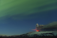 Ash plume and lava eruption from the Eyjafjallajokull volcano at night, with the Northern lights visible in the sky above, Icela