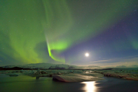 Northern lights (Aurora Borealis) and moon in sky above Jokulsarlon glacier lagoon. Southern Iceland, Europe, March 2011.