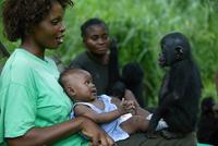 自分の赤ちゃんとボノボの子を抱く母親