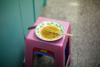 Half eaten bowl of noodles with chopsticks in, sitting on pink stool