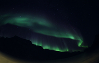Aurora Borealis casting green light at night. Greenland