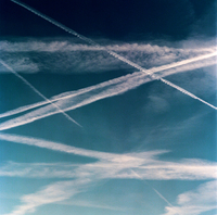 Blue sky with with graphic white marks from aeroplane trails. France