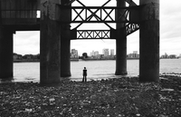 Woman underneath industrial pier