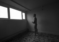 Naked man standing in en empty room lit by the window. England, United Kingdom