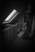 Naked man kneeling in a dark hallway lit by the window. England, United Kingdom